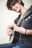 Stilvoller junger blonder Hippie-Mann, der Gitarre spielt Lizenzfreie Stockfotos