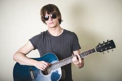 Stilvoller junger blonder Hippie-Mann, der Gitarre spielt Stockfotografie