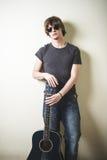 Stilvoller junger blonder Hippie-Mann, der Gitarre spielt Stockbilder