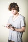 Stilvoller junger blonder Hippie-Mann, der Tablette verwendet Lizenzfreies Stockfoto