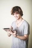 Stilvoller junger blonder Hippie-Mann, der Tablette verwendet Stockfotos