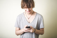Stilvoller junger blonder Hippie-Mann am Telefon Stockfoto
