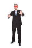 Stilvoller junger Geschäftsmann, der eine rote Augenbinde trägt Lizenzfreie Stockbilder
