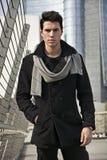 Stilvoller junger gutaussehender Mann im schwarzen Mantel, der in der Stadtzentrum-Straße steht Lizenzfreie Stockfotos