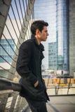 Stilvoller junger gutaussehender Mann im schwarzen Mantel, der in der Stadtzentrum-Straße steht stockbild