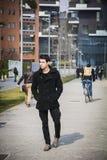 Stilvoller junger gutaussehender Mann im schwarzen Mantel, der im Stadtzentrum steht lizenzfreie stockfotos