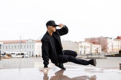 Stilvoller junger männlicher Tänzer in modernem schwarzem Kleidungstanzen-Blake-Tanz auf einer Straße in der Stadt an einem Herbs stockbild