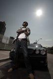 Stilvoller junger Mann, der durch ein Auto aufwirft Stockfotografie