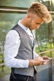 Stilvoller junger Mann, der Stellung des Telefons im Freien verwendet Lizenzfreie Stockfotografie