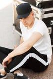 Stilvoller junger Mann in einer schwarzen Kappe mit einem weißen T-Shirt stockfoto