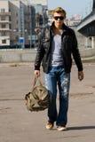 Stilvoller junger Mann geht mit großem Reisenbeutel Lizenzfreies Stockbild