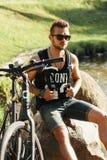 Stilvoller junger Mann mit einem Fahrrad, das auf einem Felsen sitzt Schwarzes T-Shirt w lizenzfreies stockfoto
