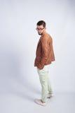 Stilvoller junger Mann steht in einer braunen Jacke Stockfotografie