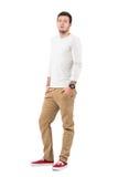 Stilvoller junger moderner Mann, der ockerhaltige Hosen und rote Turnschuhe trägt Stockbild