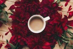 Stilvoller Kaffee und schöne rote Pfingstrosen auf rustikalem hölzernem backgr Lizenzfreies Stockbild