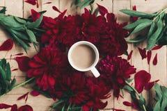 Stilvoller Kaffee und schöne rote Pfingstrosen auf rustikalem hölzernem backgr Lizenzfreie Stockfotos