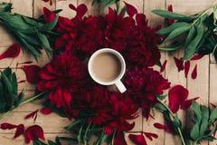 Stilvoller Kaffee und schöne rote Pfingstrosen auf rustikalem hölzernem backgr Lizenzfreies Stockfoto