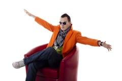 Stilvoller Kerl mit den Gläsern, die auf einem roten Stuhl sitzen Stockbild