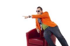 Stilvoller Kerl mit den Gläsern, die auf einem roten Stuhl sitzen Lizenzfreies Stockfoto