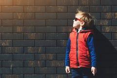 Stilvoller kleiner Junge in einer modernen Weste am sonnigen Tag, draußen auf Backsteinmauerhintergrund stockbilder