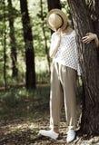 Stilvoller Mädchenjugendlicher bedeckt ihr Gesicht mit einem Strohhut stockfoto