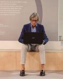 Stilvoller Mann, der am Computer an HOMI, Ausgangsinternationales Zeigung in Mailand, Italien arbeitet Lizenzfreie Stockfotos