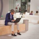 Stilvoller Mann, der am Computer an HOMI, Ausgangsinternationales Zeigung in Mailand, Italien arbeitet Lizenzfreies Stockfoto