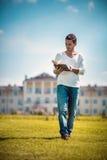 Stilvoller Mann, der das Buch im Garten liest Lizenzfreie Stockbilder