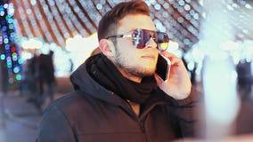 Stilvoller Mann, der herein am Telefon auf Heiliger Nacht nahe dem Hauptstadt Baum neuen Jahres, eine Reflexion der Lichter spric stock video footage