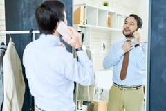 Stilvoller Mann, der am Telefon nahe Spiegel spricht Lizenzfreies Stockbild