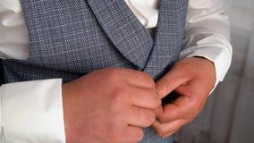 Stilvoller Mann in einer Anzugsbefestigung kn?pft auf seiner Jacke stock video footage