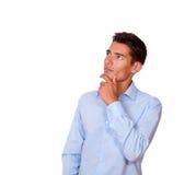 Stilvoller Mann im blauen Hemd, das reflektierend schaut. stockfotos
