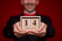 Stilvoller Mann im hölzernen Kalender des Klagengriffs, stellte am 14. Februar mit rotem Hintergrund, Fokus auf Kalender ein Stockbilder