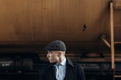 Stilvoller Mann im Retro- Blick, der auf Hintergrund der Eisenbahn aufwirft engla Lizenzfreie Stockfotos