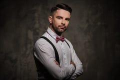 Stilvoller Mann mit der Fliege, die auf dunklem Hintergrund aufwirft Lizenzfreies Stockbild
