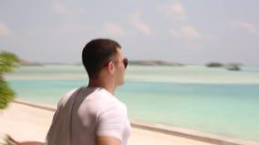 Stilvoller Mann mit Sonnenbrille verlässt seinen Bungalow auf Tropeninsel und geht zum blauen Lagunenstrand mit einem Tuch an wei stock footage