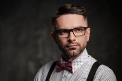 Stilvoller Mann mit tragenden Hosenträgern der Fliege und Aufstellung auf dunklem Hintergrund Stockfotografie