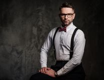 Stilvoller Mann mit tragenden Hosenträgern der Fliege und Aufstellung auf dunklem Hintergrund Lizenzfreie Stockbilder