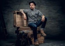 Stilvoller Mann sitzt auf einer Holzkiste Stockfotos