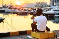 Stilvoller Mann und sein Hund, die zusammen auf Pier sitzt und bunten Sonnenuntergang genießt stockfotos