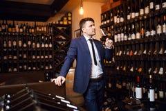 Stilvoller moderner Mann, der an Weinprobeereignis teilnimmt lizenzfreie stockfotos