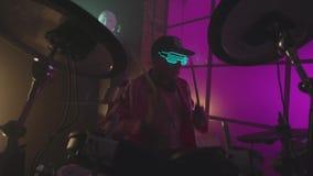 Stilvoller Musiker spielt Trommeln in einem Farbestudio ablage Stilvoller heller Mann, der Trommeln spielt stock footage