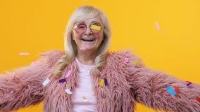 Stilvoller Pelz der netten älteren Frau, der fallende Konfettis, Festivalglück genießt stock video
