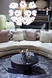 Stilvoller Raum mit halbrundem Sofa, runde Tabelle Stockbild