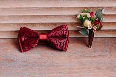 Stilvoller roter Bogen und Boutonniere auf hölzernem Hintergrund, Bräutigam, der am Morgen vor der Hochzeit fertig wird stockfotos