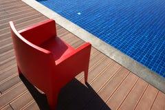 Stilvoller roter Stuhl nahe dem blauen Pool Minimalismus im Design Stockfoto
