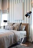 Stilvoller Schlafzimmerinnenraum mit gestreiften Kissen auf Bett Stockbild