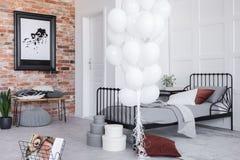 Stilvoller Schlafzimmerinnenraum mit grauer Bettwäsche und weißen Ballonen, wirkliches Foto stockfoto