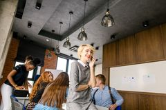 Stilvoller Sekretär ist, sprechend lachend und mit ihrem Freund am Handy Lizenzfreie Stockfotografie