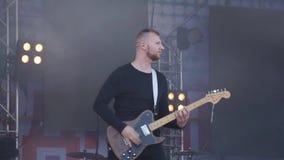 Stilvoller verrückter Rockband, der Bass-- und Solo- Gitarre mit verrückten Gefühlen und Bewegungen spielt Russland Berezniki am  stock footage